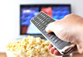 Remote control in the hand against pop-corn and TV-set — Stock Photo