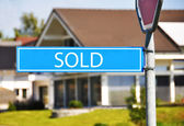 SOLD street sign against house — Stock Photo