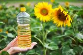 Bottle of oil against sunflowers — Stock Photo
