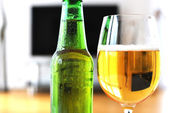 Glass of beer and a bottle against TV-set — Stock Photo