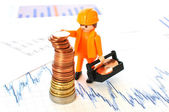 A little worker building a pyramid of coins against financial reports — Stock Photo