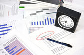 Pen and clock on the financial reports — Stock Photo