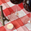 Souvenir Eiffel tower, candle and pair of wineglasses on t — Stock Photo #8317551