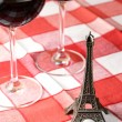 Little Eiffel tower and pair of wineglasses on table — Stock Photo #8317560