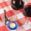 Souvenir Eiffel tower, candle and pair of wineglasses on t — Stock Photo #8317563
