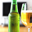 Glass of beer against TV-set — Stock Photo