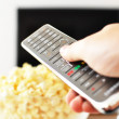 Remote control in the hand against pop-corn and TV-set — Stock Photo #8317965