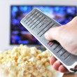 Remote control in the hand against pop-corn and TV-set — Stock Photo #8317983