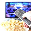 Remote control in the hand against pop-corn and TV-set — Stock Photo #8317985