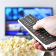 Remote control in the hand against pop-corn and TV-set — Stock Photo #8317988