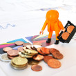 Little worker at pile of coins against financial reports — Stock Photo #8318125