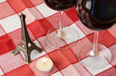 Souvenir Eiffel tower, candle and a pair of wineglasses on the t — Stock Photo