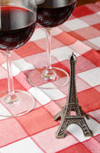 Souvenir Eiffel towe and a pair of wineglasses on the table — Stock Photo