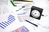 Clock, files and pen on a market report — Stock Photo