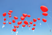 Red ballons with the messages in the blue sky — Stock Photo