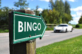 BINGO sign against sportive car on the rural road — Stock Photo