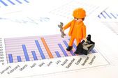 A little worker on a financial report — Stock Photo