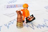 Een weinig werknemer bouwen een piramide van munten tegen financiële re — Stockfoto