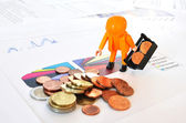 A little worker at a pile of coins against financial reports — Stock Photo