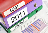 Debt, 2011, Credit folders on afinancial report — Stock Photo