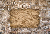 Crumbled paper on stone wall — Stock Photo
