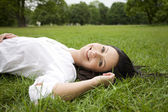 Woman laying on grass — Stockfoto