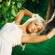 Young beautiful blonde woman near apple tree - Stock Photo