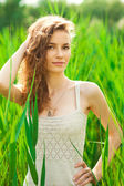 Portrait of beautiful woman in green grass — Stock Photo