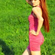 Young beautiful redhead woman on grass — Stock Photo