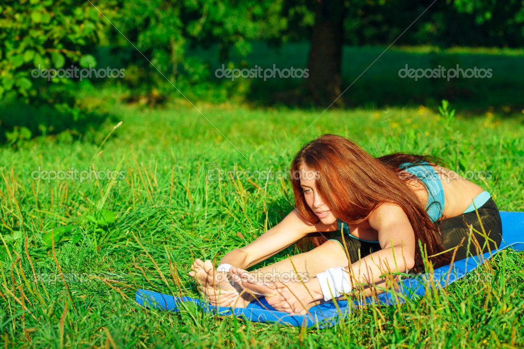Young woman doing yoga exercise on green park — Stock Photo #9354439