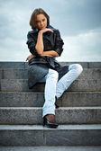 Beautiful young woman sitting on stone steps — Stock Photo