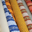 Rolls of Provencal textile on a market stall — Photo