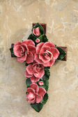 Cross ornament with ceramic flowers in France — Stock Photo