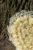 Detail of white floral arramgement near a tree — Stock Photo