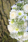 Detail of white floral arrangement near a tree — Stock Photo