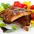 Tasty grilled ribs with vegetables — Stock Photo