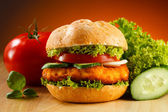 Big hamburger and vegetables — Stock Photo