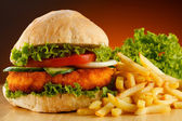 Big hamburger, French fries and vegetables — Stock Photo