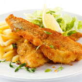 Fish dish - fried fish fillet, French fries with vegetables — Stock Photo