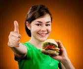 Fille mangeant signe ok de la grosse hamburger montrant — Photo