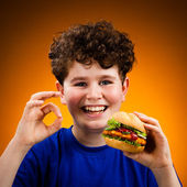 Boy eating big sandwich showing OK sign — Stock Photo
