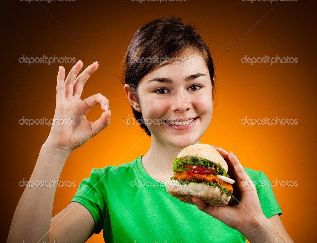 Girl eating big hamburger showing OK sign — Stock Photo #10531873