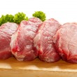 Raw pork on cutting board and vegetables -  