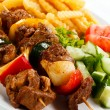 Grilled meat, French fries and vegetables - Stockfoto