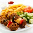 Grilled meat, French fries and vegetables - Foto Stock