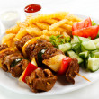 Grilled meat, French fries and vegetables -  