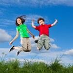 dívka a chlapec běh, skákání venkovní — Stock fotografie #8410766