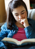 Girl reading book at home — Stock Photo