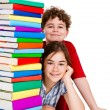 Students sitting behind pile of books on white — Stock Photo