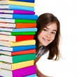 Student sitting behind pile of books on white — Stock Photo